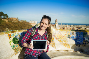 Pretty young female tourist having break and surfing the internet at digital tablet in Parc Guell in Barcelona, Spain.