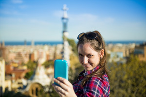 Pretty young female tourist takes selfie in Parc Guell in Barcelona, Spain.