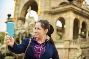 Pretty young female tourist taking selfie in front of the historical building in Barcelona, Spain.