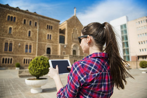 Pretty young female tourist using electronic tablet in front of the church in Barcelona, Spain.