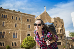 Pretty young female tourist with backpack in front of the church in Barcelona, Spain.