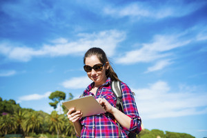 Pretty young female tourist with backpack using digital tablet, portrait with blue sky