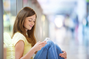 Pretty young girl sitting in a shopping mall and using her smartphone