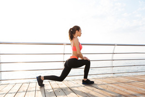 Pretty young woman athlete doing exercises on wooden terrace in the morning