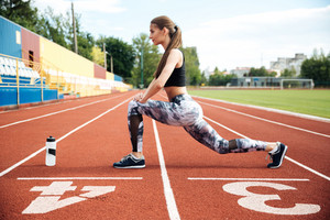 Pretty young woman athlete working out on stadium