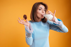 Pretty young woman eating cookies and drinking milk over yellow background