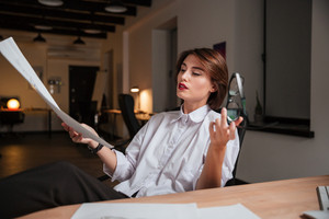 Pretty young woman fashion designer sitting with legs on table and looking at sketches in office