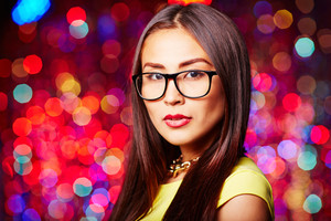 Pretty young woman in eyeglasses looking at camera at party