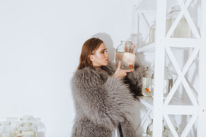 Pretty young woman in fur coat putting gold fish in jar on the shelf