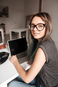 Pretty young woman in glasses working with blank screen laptop at home