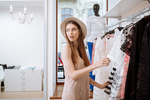 Pretty young woman in hat choosing clothes and doing shopping in clothes shop