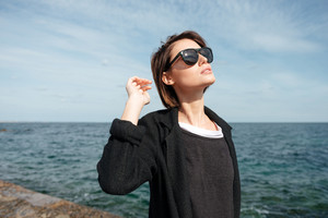 Pretty young woman in sunglasses walking near the sea in sunny weather