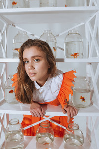 Pretty young woman leaning on the shelf with gold fishes in jars