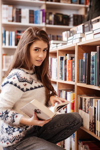 Pretty young woman looking for books in a book shelf in library