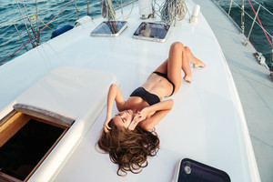 Pretty young woman lying on the yacht and talking on the smartphone