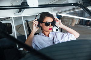 Pretty young woman pilot in headset ready to fly in small airplane