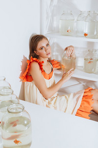 Pretty young woman sitting and holding gold fish in jar in the room