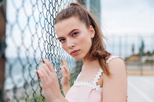 Pretty young woman standing outdoors near chain link fence