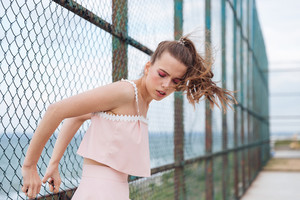 Pretty young woman standing with eyes closed near chain link fence
