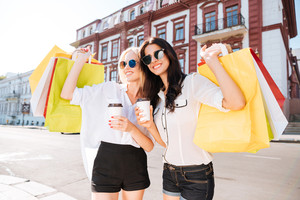 Pretty young women with shopping bags having fun walking on the street