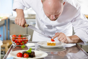 Professional chef decorates dessert cake with strawberry in kitchen