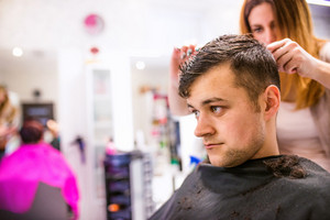 Professional hairdresser cutting hair of her young client, making a new haircut. Barber at work. Man at barbershop.