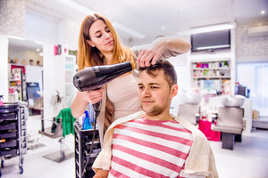 Professional hairdresser drying hair to her handsome client. Barber at work. Man at barbershop.