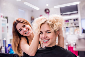Professional hairdresser making new haircut to her beautiful blond client.