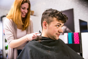 Professional hairdresser shaving head of her young client, making a new haircut. Barber at work. Man at barbershop.