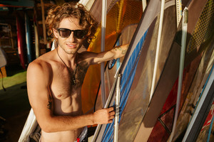 Professional young surfer getting surf board ready to catch waves at the beach
