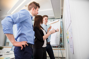 Professionals Looking At Plans Stuck On Wall In Office