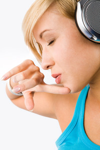 Profile of attractive teenage girl with headphones listening to music and thinking about something