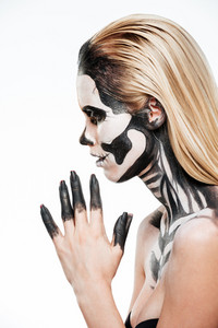 Profile of girl with terrifying halloween makeup over white background