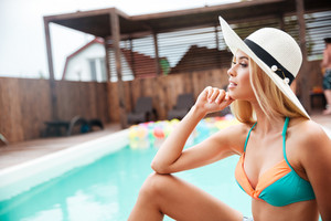 Profile of sensual young woman in hat with long blonde hair near swimming pool