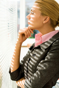 Profile of serious woman looking through venetian blind and thinking about something