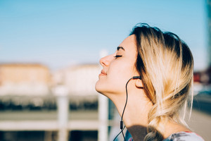 Profile portrait of young beautiful caucasian woman listening music with earphones, eyes closed, smiling - music, relaxing, serenity concept