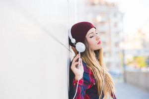Profile portrait of young handsome caucasian blonde hair woman leaning against a wall, listening music with headphones, eyes closed - serene, enjoying, music concept