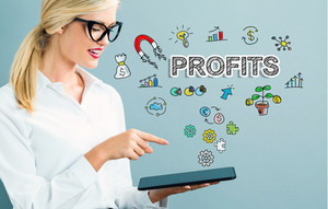 Profits text with business woman using a tablet