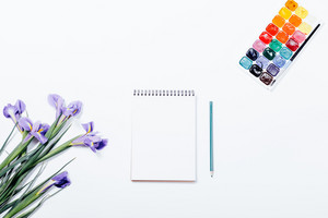 Purple flowers, notebook, pencil and watercolor palette of colors on a white table top view