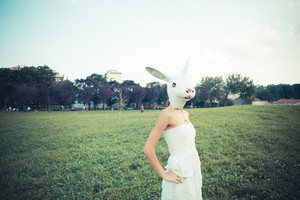 rabbit mask absurd beautiful young woman with white dress in the city