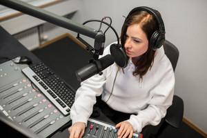 Radio Jockey Using Music Mixer While Communicating On Microphone