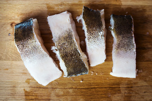 Raw zander fish fillets on a wooden cutting board.