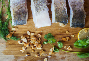 Raw zander fish fillets with roasted almonds and herbs on a wooden cutting board.
