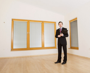 Real Estate Agent is standing in new empty house.
