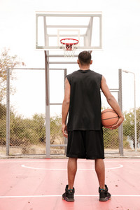 Rear view of a basketball player looking at hoop, shooting at basket outdoor.