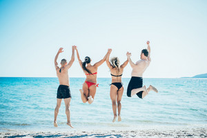 Rear view of a multiethnic group of friends jumping into water during summer vacation - achievement, goal, friendship concept