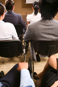 Rear view of business people listening attentively while sitting at conference