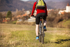 Rear view of cyclist man riding mountain bike on outdoor trail in nature