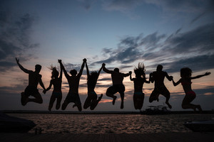 Rear view of friends jumping into water during summer vacation in front of a sunset