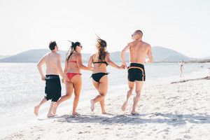 Rear view of group of friends millennials running holding hands on the seashore having fun - friendship, interaction, happiness concept